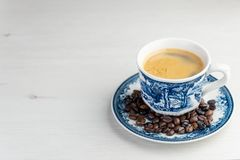 Front view of a delicious and tasty old and rustic cup of freshly made coffee with coffee beans stock photography