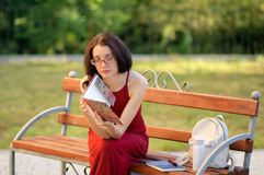 Front View des jungen Mädchens in Eyesglasses und lang in rotem Kleid, die auf der Bank im Stadt-Park sitzen und irgendein Buch l Lizenzfreies Stockbild