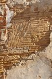 Artisan crafted exterior building wall on deserted street in Spain. Front view of deteriorating, artisan crafted exterior building wall of brick, covered with royalty free stock images