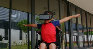 Front view of disabled African American schoolboy using virtual reality headset in school corridor 4. Front view of disabled African American schoolboy using stock footage