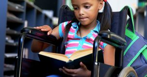 Front view of disabled African American schoolgirl reading a book in library at school 4k stock video