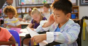 Front view of disabled asian schoolboy studying in the classroom 4k stock video