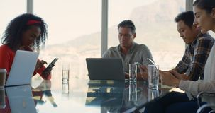 Business executives sitting at table and working in modern office 4k. Front view of diverse business executives sitting at table and working in modern office stock video footage