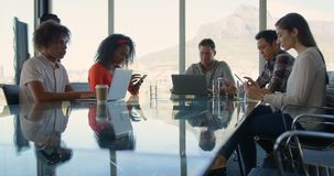 Business executives sitting at table and working in modern office 4k. Front view of diverse business executives sitting at table and working in modern office stock video
