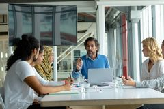Business people discussing with each other in meeting at conference room in a modern office. Front view of diverse business people discussing with each other in stock photos