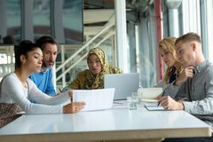 Business people discussing over document at table in a modern office. Front view of diverse business people discussing over document at table in a modern office royalty free stock photos