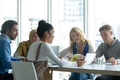 Business people discussing over document at table in a modern office. Front view of diverse business people discussing over document at table in a modern office royalty free stock image