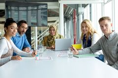 Business people looking at the camera during a business meeting in a modern office. Front view of diverse business people looking at the camera during a business royalty free stock photo