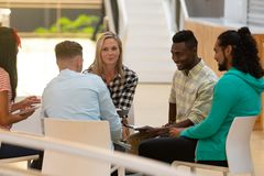 Business people sitting together and having a group discussion in a modern office. Front view of diverse business people sitting together and having a group royalty free stock images