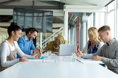 Business people working together in meeting room in a modern office. Front view of diverse business people working together in meeting room in a modern office royalty free stock photography