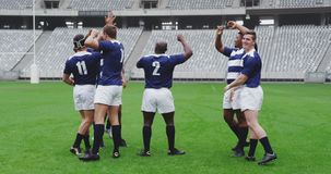Male rugby players celebrating goal in ground at stadium 4k. Front view of diverse male rugby players celebrating goal in ground at stadium. They are smiling and stock footage