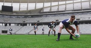Male rugby players playing rugby match in stadium 4k. Front view of diverse male rugby players playing rugby match in stadium. Caucasian male player passing stock video footage