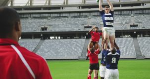 Rugby players playing rugby match in stadium 4k. Front view of diverse rugby players playing rugby match in stadium. They are catching rugby ball 4k stock video