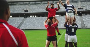 Rugby players playing rugby match in stadium 4k. Front view of diverse rugby players playing rugby match in stadium. They are catching rugby ball 4k stock video footage