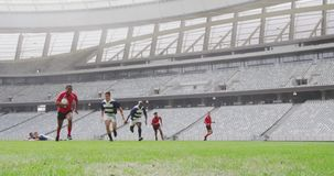 Rugby players playing rugby match in stadium 4k. Front view of diverse rugby players playing rugby match in stadium. He is jumping on goal line 4k stock footage