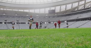 Rugby players playing rugby match in stadium 4k. Front view of diverse rugby players playing rugby match in stadium. Male player jumping on the ground 4k stock footage