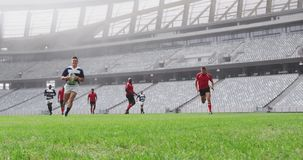 Rugby players playing rugby match in stadium 4k. Front view of diverse rugby players playing rugby match in stadium. Male player jumping on the ground 4k stock video