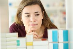 Customer choosing medicines in a pharmacy. Front view of a doubtful customer choosing medicines in a pharmacy Royalty Free Stock Photos