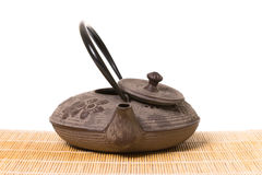 Front view of eastern iron teapot with a half opened lid on wooden mat Royalty Free Stock Photography