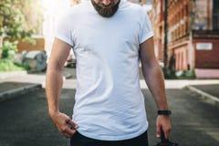 Front View El hombre milenario barbudo joven vestido en la camiseta blanca es soportes en la calle de la ciudad Mofa para arriba imagenes de archivo