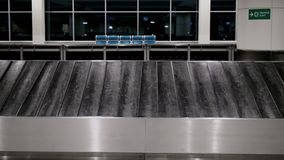 Empty luggage belt in airport terminal. Front view of empty luggage belt moving slowly in empty airport arrival terminal. Concept lost items, suitcases, baggage stock video