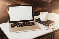 Front view. Empty workplace. On white coffee table is laptop with blank screen, cup of coffee, notebook, pen, newspaper. Royalty Free Stock Photography