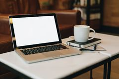 Front view. Empty workplace. On white coffee table is laptop with blank screen, cup of coffee, notebook, pen, newspaper. Royalty Free Stock Photos