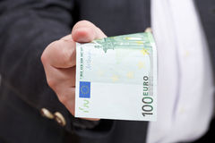 Front view 100 euro banknote in businessman hand. Front view of 100 euro banknote in businessman hand close up Stock Photo