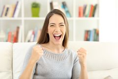Front view of an excited woman looking at camera at home. Front view portrait of an excited woman looking at camera sitting on a sofa at home Royalty Free Stock Images