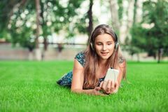 Front view of a fashion girl listening music with headphones and smart phone royalty free stock image