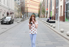 Front view of a fashion happy girl walking and using a smart pho. Ne on a city street Royalty Free Stock Photo