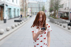 Front view of a fashion happy girl walking and using a smart phone. On a city street Royalty Free Stock Photography