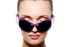 Front view of female face in violet sunglasses Royalty Free Stock Images