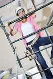 Front view of female worker climbing on scaffold Royalty Free Stock Photography