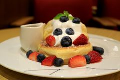 Fluffy Souffle Pancake with Fresh Whipped Cream and Mix Berries on White Plate with Syrup Pitcher royalty free stock images