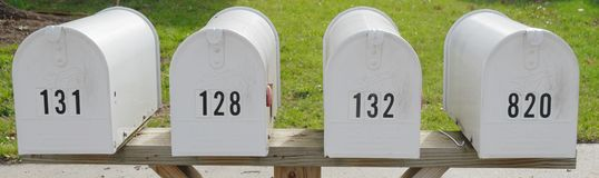 Front View of four white mailboxes Royalty Free Stock Photography