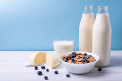 Front view of fresh dairy products and cereals with blueberries on a white wooden table and blue background. Shallow depth of fiel Stock Photos