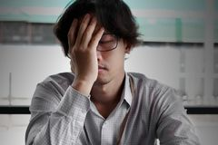 Front view of frustrated stressed young Asian business man covering face with hands and feeling tired with job. Royalty Free Stock Images