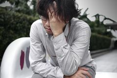 Front view of frustrated stressed young Asian business man with hands touching head and feeling disappointed or exhausted with job.  Royalty Free Stock Images