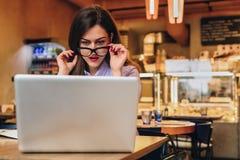 Front View Geschäftsfrau sitzt im Café vor Laptop und betrachtet Schirm in der Überraschung und senkt ihre Gläser Stockfoto
