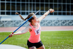 Front view of girl athlete in sportswear throwing javelin. Chelyabinsk, Russia - June 16, 2015: A girl athlete competing in the javelin throw during Championship Royalty Free Stock Photos