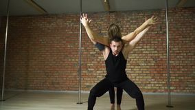 Front view of a girl in dance rests on the back of your partner. Front view of a girl in dance lies on his back on his partner`s brick wall background stock footage