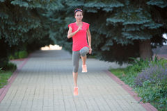 Front view of a girl doing exercise outdoor in a park, jogging Royalty Free Stock Images