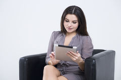 Front view of girl in gray looking at tablet Royalty Free Stock Image