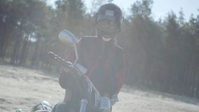 Front view of the girl in the helmet standing at the motorcycle in front of pine forest in sunlight. Hobby, traveling. Front view of the girl in the helmet and stock video