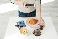 Front view of girl holding phone while shooting tasty breakfast. Girl holding phone, shooting tasty breakfast for modern stylish photography. Healthy nutritios Royalty Free Stock Photography