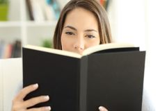 Front view of a girl reading a book at home Royalty Free Stock Images