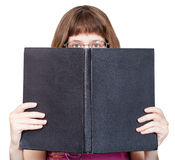 Front view of girl with spectacles looks over book Stock Images