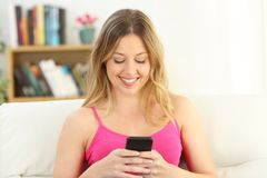 Front view of a girl using a smart phone at home Stock Photos