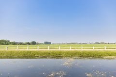 Front view of green agricultural field with white fence,lake and sky stock photo